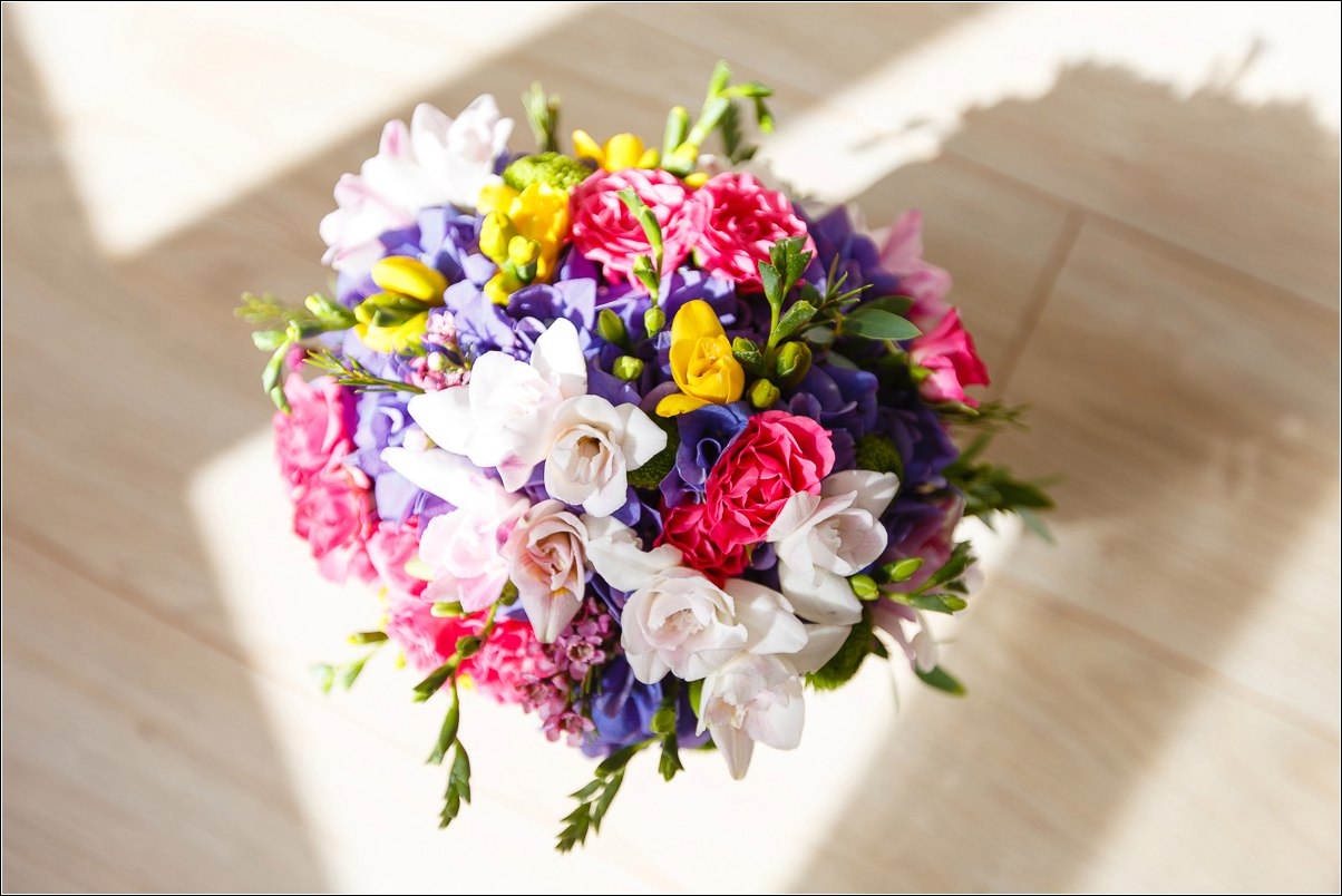 Bridal and prom bouquet in rainbow color with freesia, hydrangea and lisianthus.