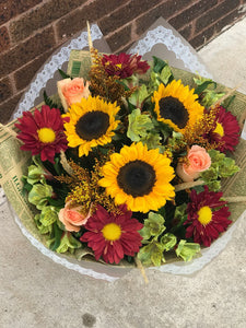 Bring the beauty of the outdoors in with this wildly wondrous bouquet, featuring the classic hues of autumn.  Includes:  Sunflowers, orange chrysanthemums, peach roses, solidago, yellow alstroemerias. Free message card