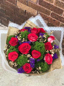 Bold and beautiful! This gorgeous arrangement is a stunning statement of devotion!  Includes:  Red roses, stacice, gold berries, assorted greens. Free message card