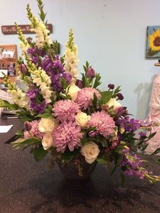 This stunning arrangement of purple sider chysanthemums and lavender snapdragons will express your sympathy lovingly and tastefully.  Includes:   Lavender snap dragons, white roses, lavender spider chrysanthemums with assorted greenery. Delivered in a basket or vase. Free message card