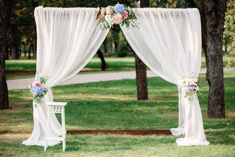 Many brides want their wedding ceremony to have a gorgeous and personalized backdrop, because it is in front of this arch that many magic and touching moments occur, and many memorable photos are taken. Wedding arch with flowers and fabrics. Includes: White chiffon fabrics Flowers: white chrysanthemums, pink and light blue hydrangea, assorted greens. Wood stand Dimensions: width 78'', height 86''