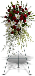 Funeral arrangement on holder with red roses, lylies and orchids.