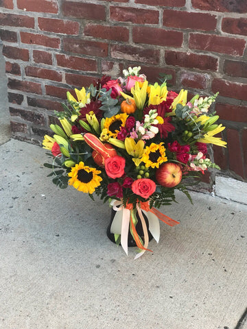Warm their hearts and brighten their table with this lush fall bouquet, arranged in glass vase.  Includes:  Sunflowers, pink roses, orange chrysanthemums, yellow lilies and snap dragons, assorted greens. Artificial pumpkins and apples. Vase Free message card