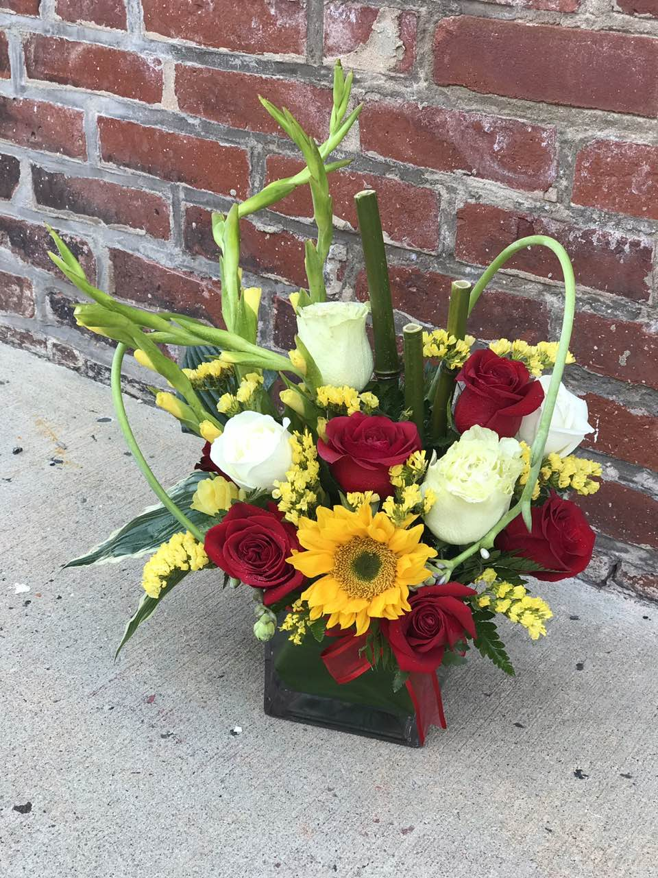 The cheerful autumn floral arrangement is rich with color, making it a stylish, energizing pick for any fall occasion.  Includes:  Sunflower, red and white roses? yellow statice and gladioli, bamboo.  Cube vase Free message card