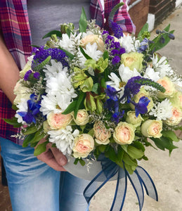 Like gazing into a clear blue sky, this serene arrangement soothes the soul and cheers the heart. Its creamy roses and snowy daisies are arranged in velvet box.  Includes:  White daisies, creamy mini roses, yellow alstroemerias, blue delphinium, blue veronica. Velvet box Free message card