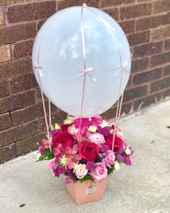 Welcome the newest little cutie into the world with this pink-tastic box. Decorated like air balloon, it's a darling little bundle - just like her.  Includes:  Pink roses, pink alstroemerias, white daisies, pink lisianthus, assorted greens. Balloon Floral box Free message card