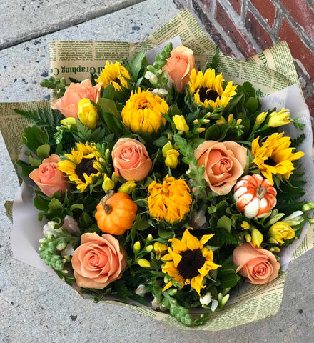 A burst of beauteous blooms in autumn shades of orange and yellow is mixed with a funny pumpkins. A splendid gift for birthdays or any fall occasion.  Includes:  Sunflowers, peach roses, white and yellow freesias, yellow snap dragons, assorted greens.  Artificial pumpkins Wrapped in a craft paper Free message card