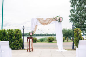 Many brides want their wedding ceremony to have a gorgeous and personalized backdrop, because it is in front of this arch that many magic and touching moments occur, and many memorable photos are taken. Wedding arch with flowers and fabrics. Includes: White chiffon fabrics Flowers: white chrysanthemums, pink hydrangea, assorted greens. Metal stand Dimensions: width 78'', height 86''