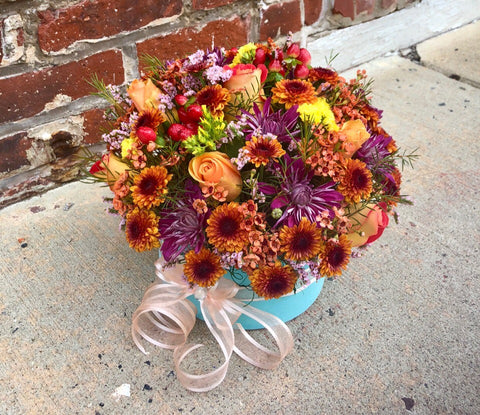 Capture the natural beauty of autumn with this stunning arrangement in an elegant box, sure to brighten any fall day.  Includes:  Purple chrysanthemums, brown daisies, red alstroemerias, orange wax flowers, solidago, peach roses.  Velvet box Free message card