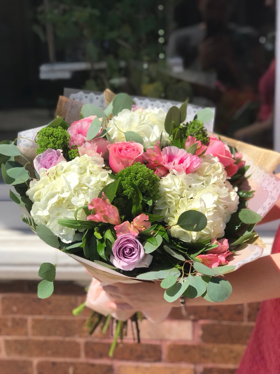 In the prettiest shade of whisper-soft pink, this breathtaking bouquet proclaims your affection in a most powerful way!    This delicate arrangement includes pink alstroemeria, white hydrangea, leatherleaf fern, and eucalyptus leaf.