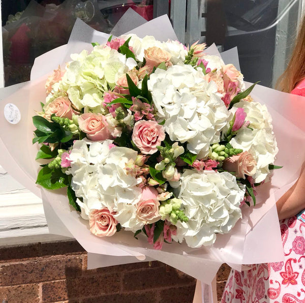 Stunning in its simplicity, this innocent harmony of light pink roses and snow white hydrangeas are a heartfelt way to send your very best.  Includes:  White hydrangea, light pink roses, pink alstoemerias, assorted greens. Wrapping in a craft paper. Free message card