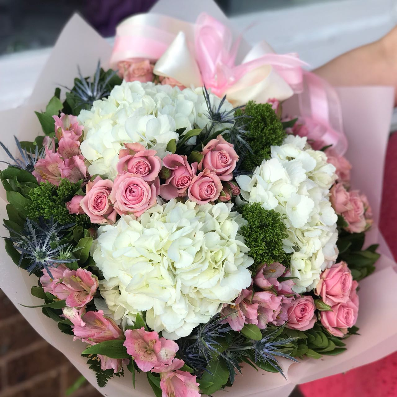 Would you walk a mile for one of her smiles? You can bet she'll be walking toward you, arms outstretched, when she receives this gorgeous. And wait till you see the smile she gives you.  Includes:  White hydrangea, pink mini roses, pink alstroemeria, eringium, assorted greens. Free message card