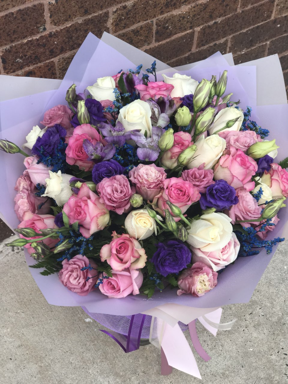 Whatever the occasion - when you truly want to spoil her, send this luxurious lavender arrangement! Deluxe and dramatic, this mix of flowers is a gift she won't soon forget.  Includes:  Pink roses, purple and pink lisianthus, white roses, blue limonium, fern. Wrapped in a craft paper Free message card