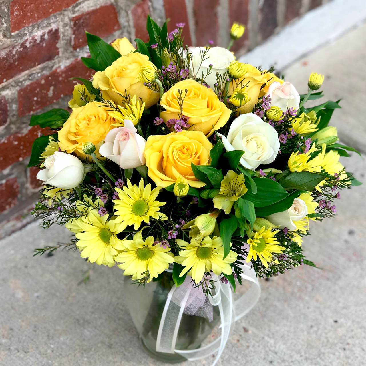 Would you walk a mile for one of her smiles? You can bet she'll be walking toward you, arms outstretched, when she receives this gorgeous array. And wait till you see the smile she gives you.  Includes:  Yellow and white roses, yellow alstroemeria, yellow daisies, wax flowers, fern. Vase Free message card