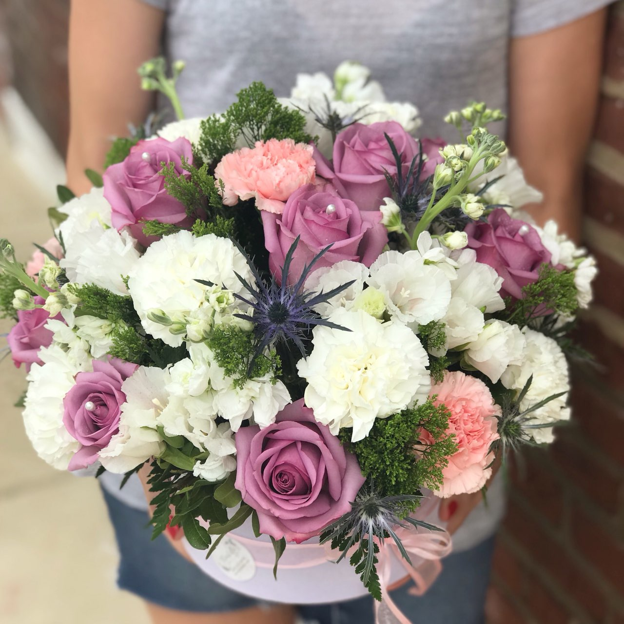 They'll fall in love with this pretty, playful bouquet!  It's a fresh mix they'll adore for any occasion.  Includes:  Purple roses, pink and white carnations, eringium, white stock, assorted greens. Velvet box Free message card