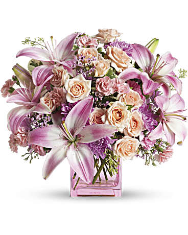 Peach, pink and lavender blooms are a sweet and innocent way to show your affection.  Includes:  Pink lilies, creamy mini roses, lavender daises, assorted greens. Vase Free message card