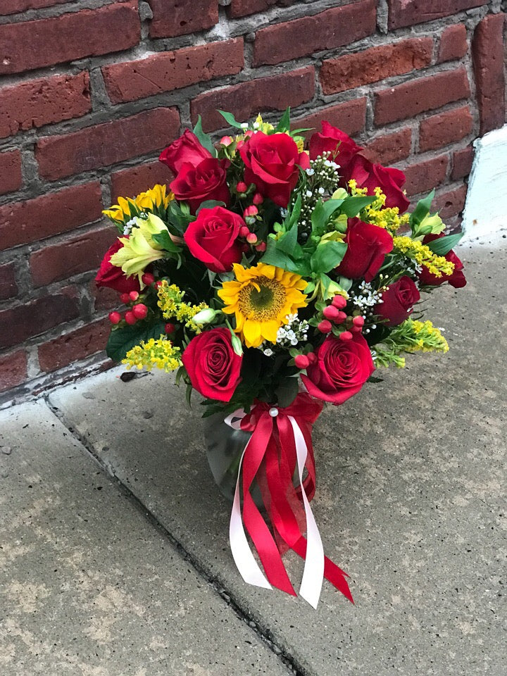 Happy yellow sunflowers and red roses bring sunshine to your Thanksgiving!  Includes:  Red roses, sunflowers, solidago, red berries,assorted greens. Vase Free message card