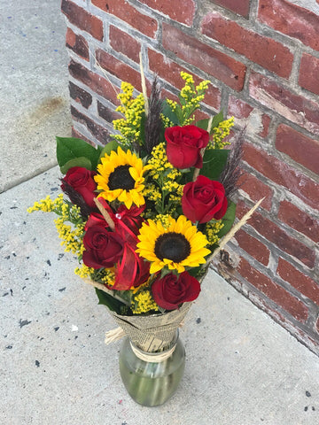 A gift of pure joy!  You know someone who could use a lift. Give it to them the easy way. Just give us a click.  Includes:  Red roses, sunflowers, solidago,assorted greens. Free message card