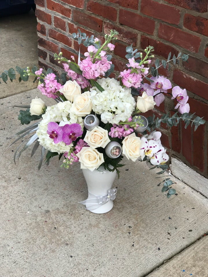 She'll always be your #1 lady. Remind her just how special she is - send a sensational gift she'll never forget. This beautiful bouquet  is sure to make an impression!  Includes:  White hydrangea, pink stock, white roses, pink orchids, eucalyptus. Vase Free message card