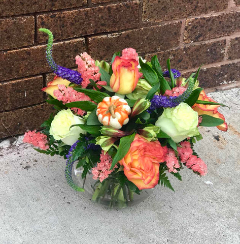 Greet a loved one with the golden glow of autumn. Like a trip to the Tuscan countryside, this garden of fall flowers warms the heart with its orange and gold blooms.  Includes:  Orange and white roses, yellow alstroemerias, peach statice, blue veronica. Artificial pumpkin. Free message card