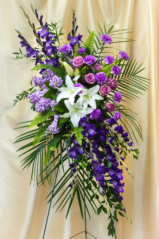 Funeral arrangement on a holder of lilies, purple stock, gladiolus and roses.