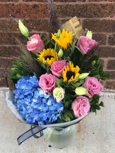 A simply splendid way to surprise someone special! This sophisticated, sunshiny arrangement of hydrangea and roses is an instant pick-me-up!  Includes:  Blue hydrangea, pink lisianthus, sunflowers, assorted greens. Wrapped in a craft paper. Free message card