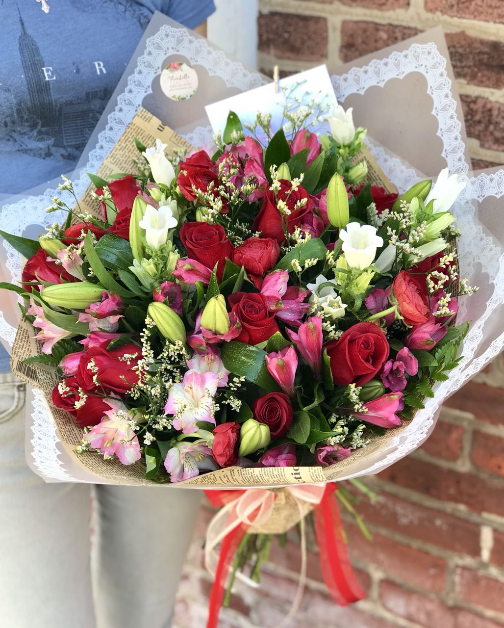 "Whether for your significant other or your sister, aunt or grandmother, this delightful floral gift is a sweet way to say ""I love you.""  Includes:  Red roses, bells, pink alstroemeria, white lilies, limonium, assorted greens. Wrapped in craft paper. Free message card"