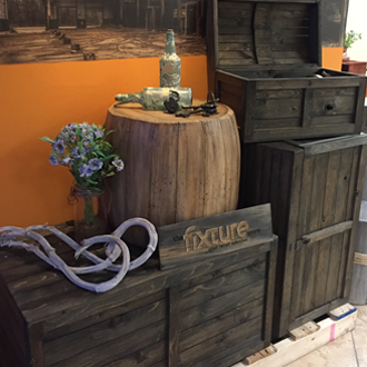 The rustic crate series 300 stained with onyx and set up as a retail wine display with driftwood and a barrel