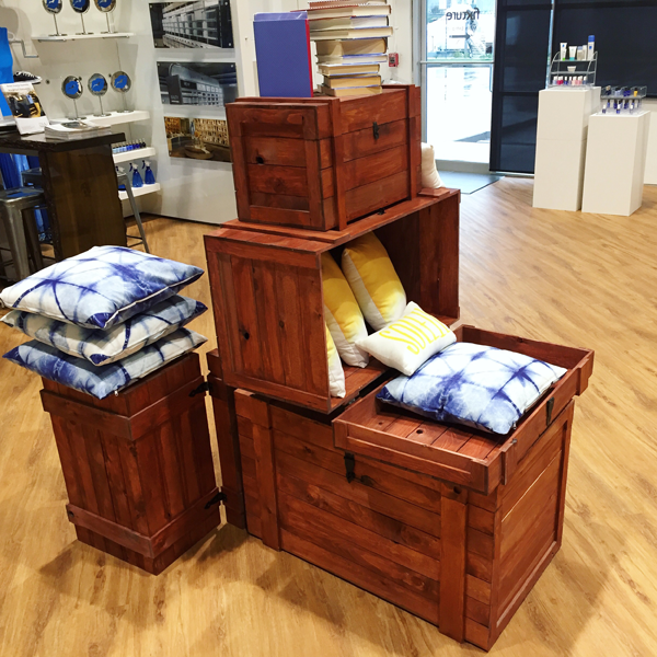 The rustic crate series 400 with crimson stain set up as a spring display with blue and yellow pillows and books
