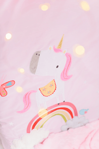 Girls pink cot bed quilt featuring a stunning unicorn and rainbow applique, the perfect cot bed quilt for any little girls nursery.