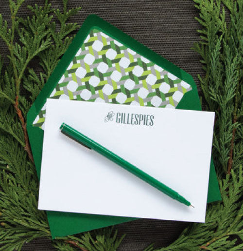 Letterpress stationery printed with a family name in green ink with dark green envelopes.