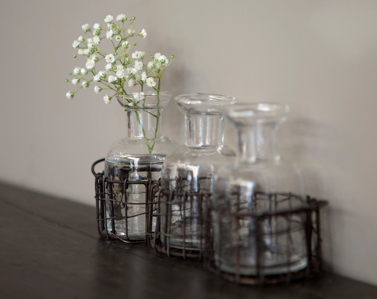Set of 3 glass bottles in wire holder