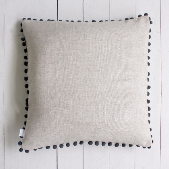 Natural cushion with grey pom poms