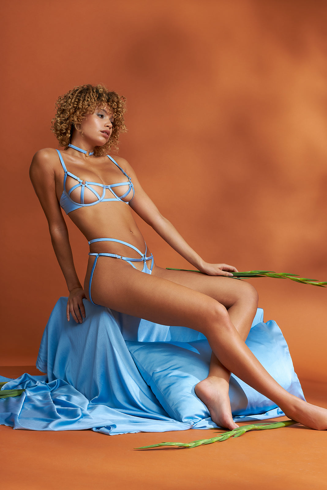 Model wears a cage bra and ouvert knicker crafted from soft blue peace silk