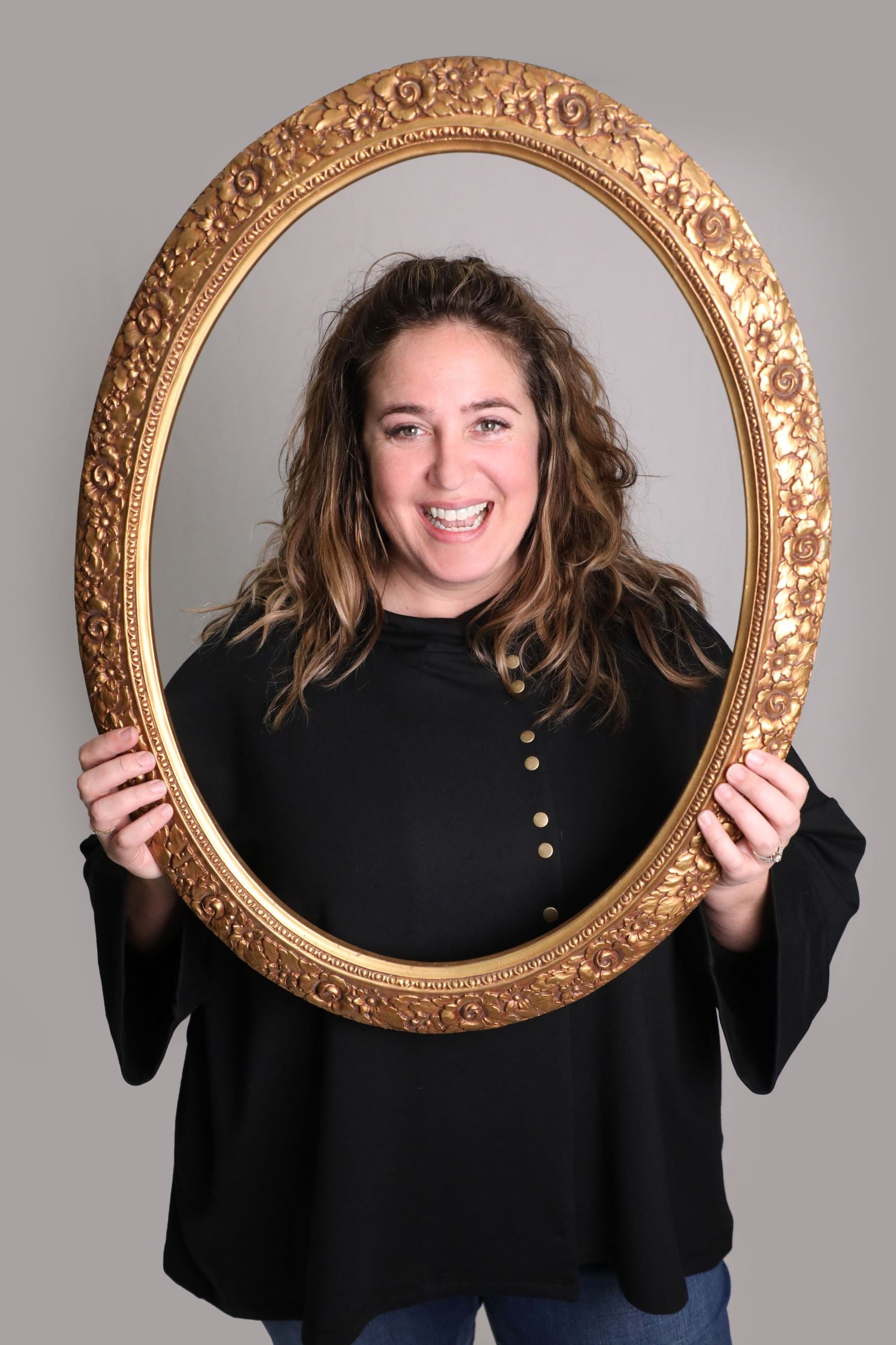 Woman smiling using a gold frame as a prop to frame the shot