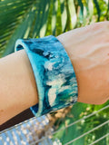 Blue and white resin swirl wide bangle. Shown on models arm. Junction 44.