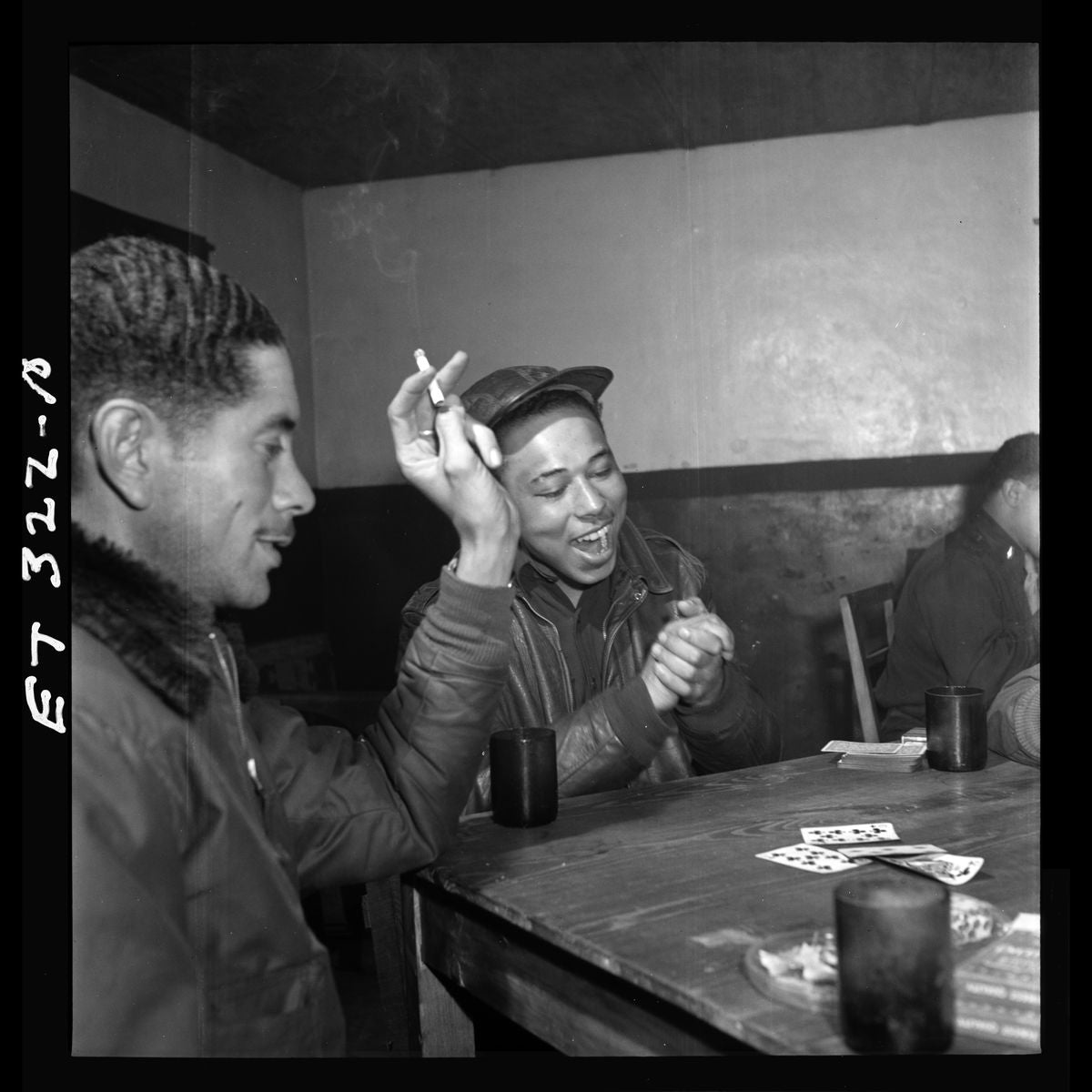 Tuskegee airmen playing cards in the officers' club in the evening by Toni Frissell - March 1945