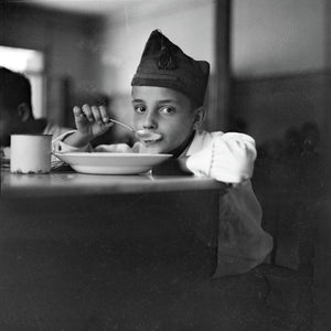 Child looking up from eating soup, Madrid by Gerda Taro - 1936-37