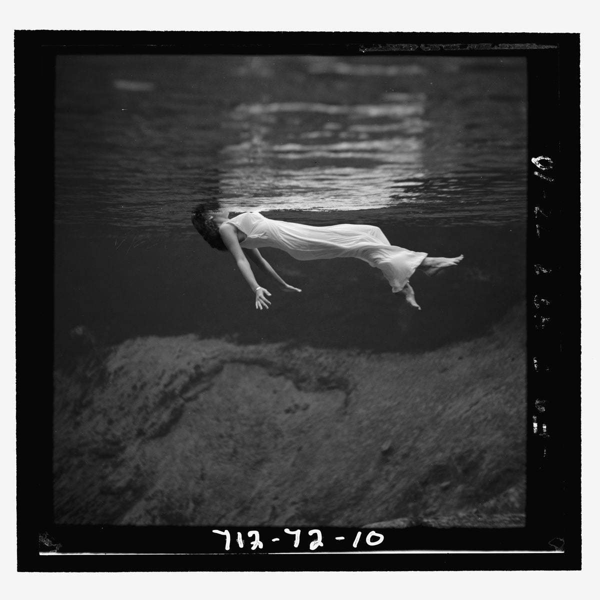 A woman, wearing a long gown, floating in water by Toni Frissell - 1947