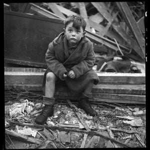 Boy seated in wreckage of building after a bombing raid of London during World War II January 1945