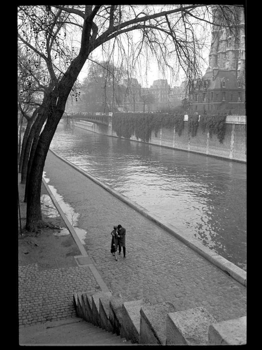A couple walking along the Seine River in Paris by Toni Frissell - c.1955