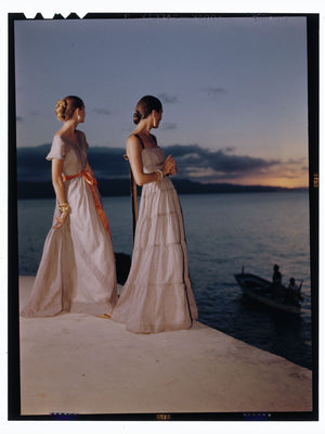 Two women in evening gowns posed in front of water at sunset Nov 1946 Toni Frissell