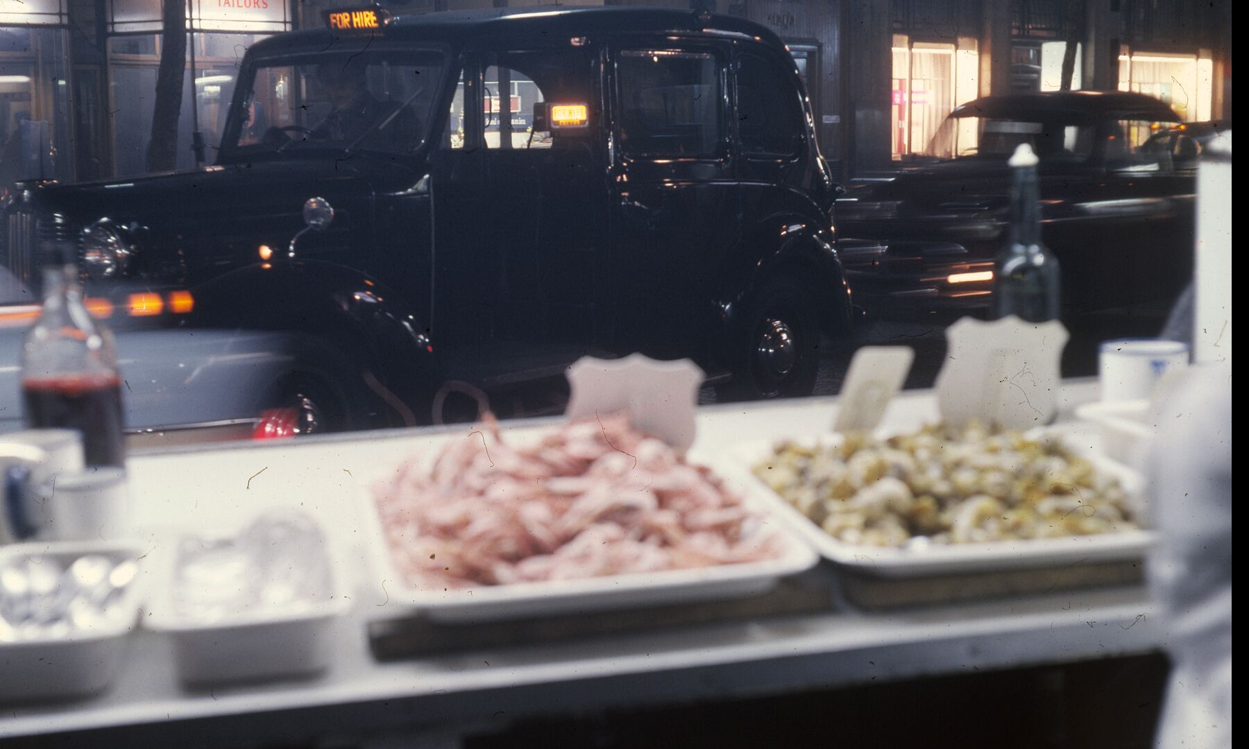 London Cabs and Seafood by Bob Hyde. Taken in the West End of London in the 1960s.