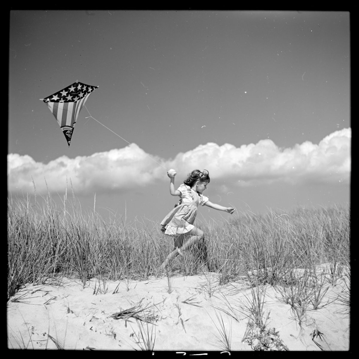 Photograph shows Toni Frissell's daughter, Sidney Bacon (Frissell) Stafford, running on a beach with a kite in Southampton, Long Island, New York in 1944 - by Toni Frissell.