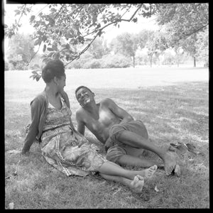 Woman and man seated on grass near trees by Toni Frissell - c.1955