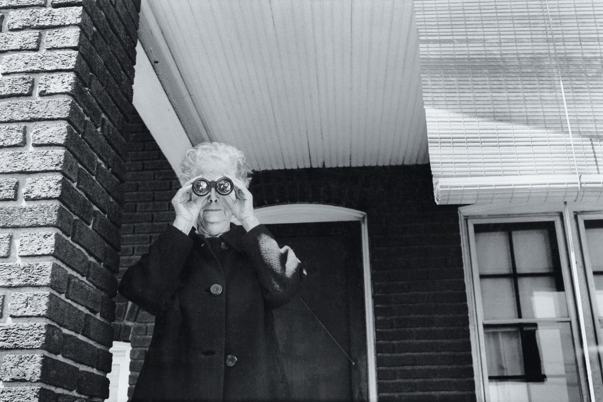 Woman Looking at a Parade from her Front Porch in Ohio by Michael Carlebach - 1972