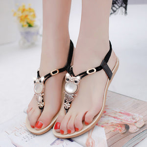 Flat women sandals elastic t-strap with large rhinestone owl pendant.