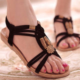 Flat tiki style accents sandals and geometric carvings with rope cross-tied back straps.