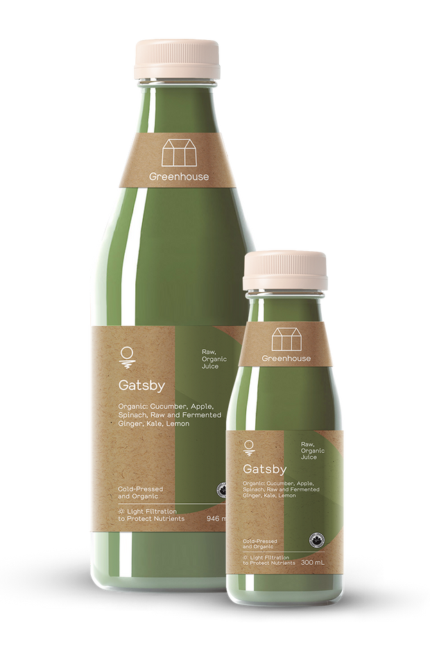 Two glass bottles of Gatsby made with cold-pressed organic cucumber, apple, spinach, kale, ginger, and lemon.