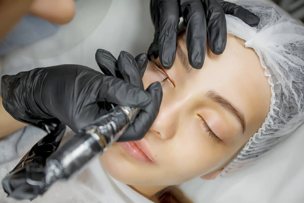 A woman having permanent eyeliner applied.